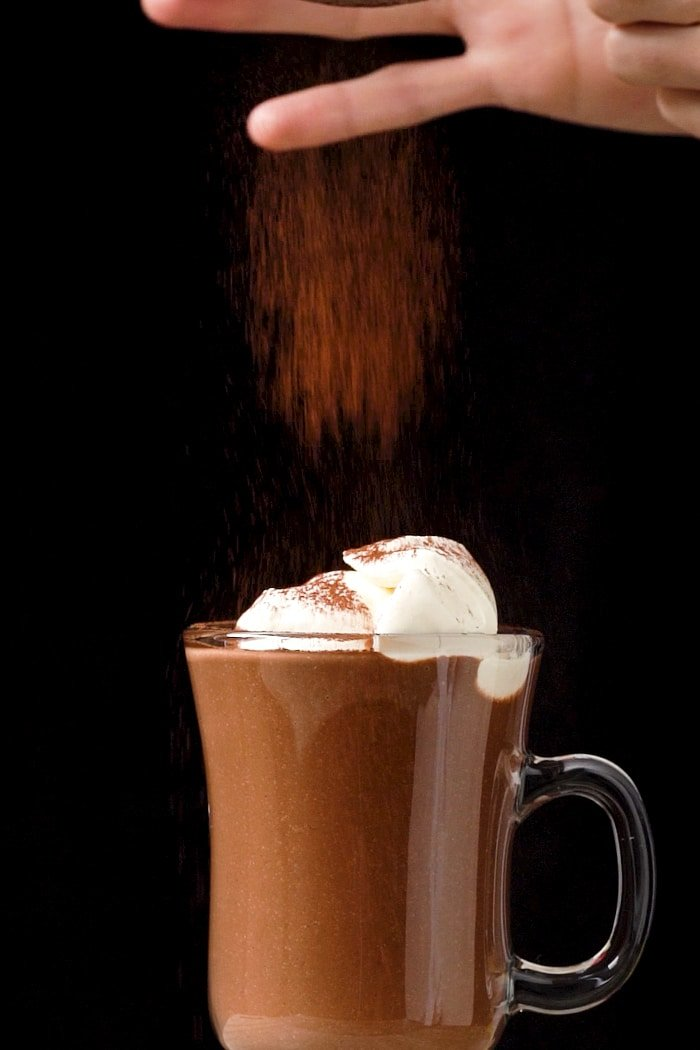 Adding a sprinkle of cocoa to a keto hot chocolate