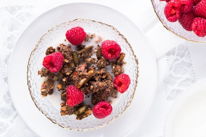Keto granola in a bowl with raspberries and milk