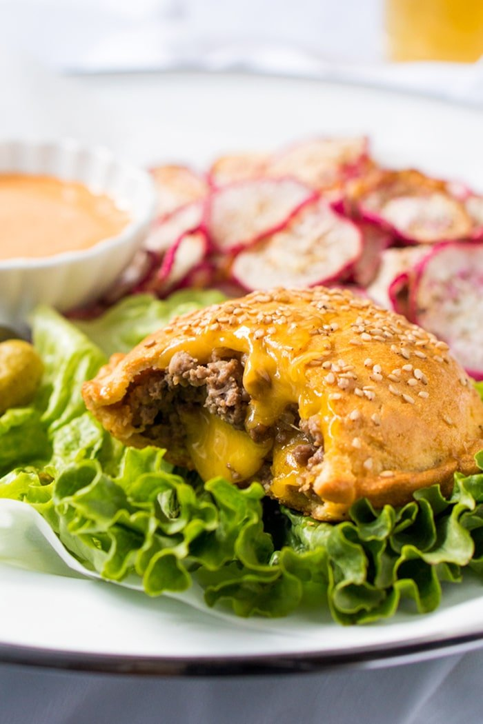A keto cheeseburger on a plate with lettuce and 'fries'