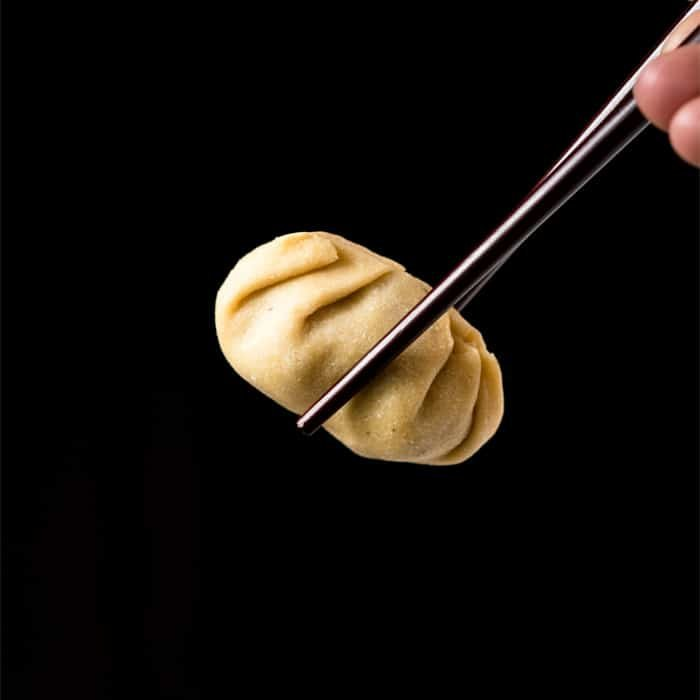 Holding a keto dumpling with chopsticks