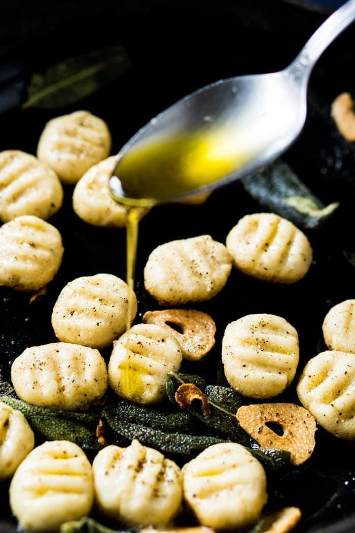Drizzling olive oil onto keto ricotta gnocchi