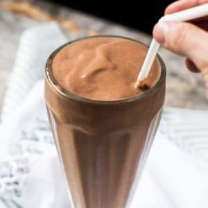 Drinking a keto chocolate milkshake with a straw