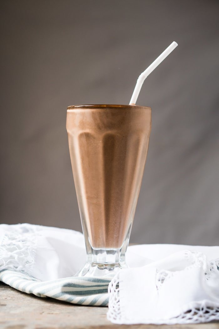 A paleo and keto chocolate milkshake in a tall glass with a straw