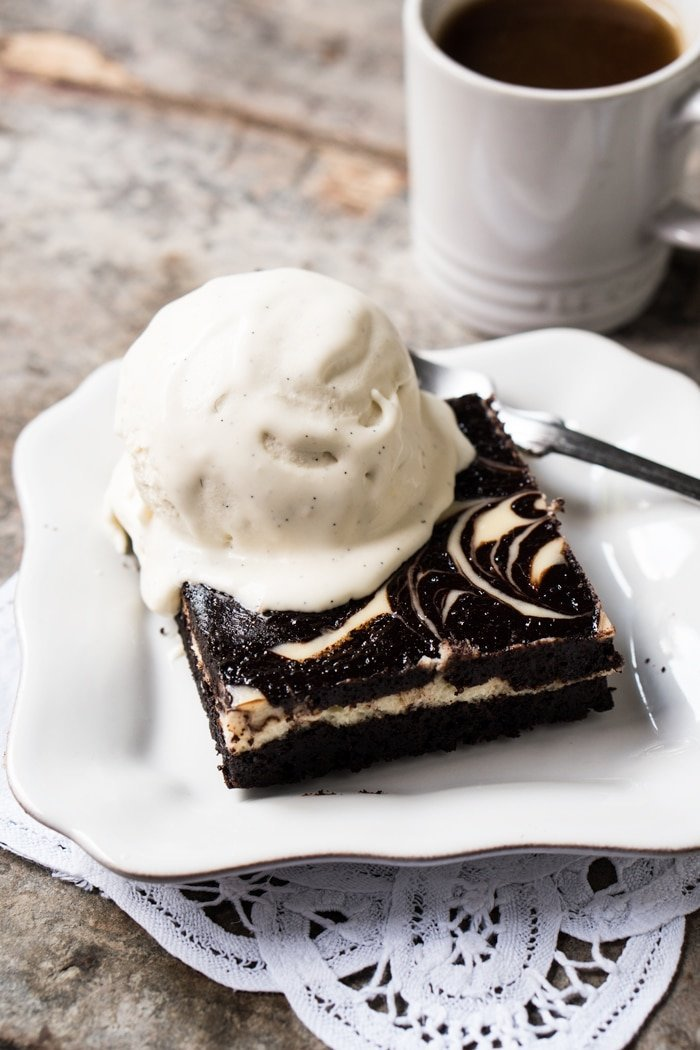 A slice of keto cheesecake brownie with a scoop of vanilla ice cream