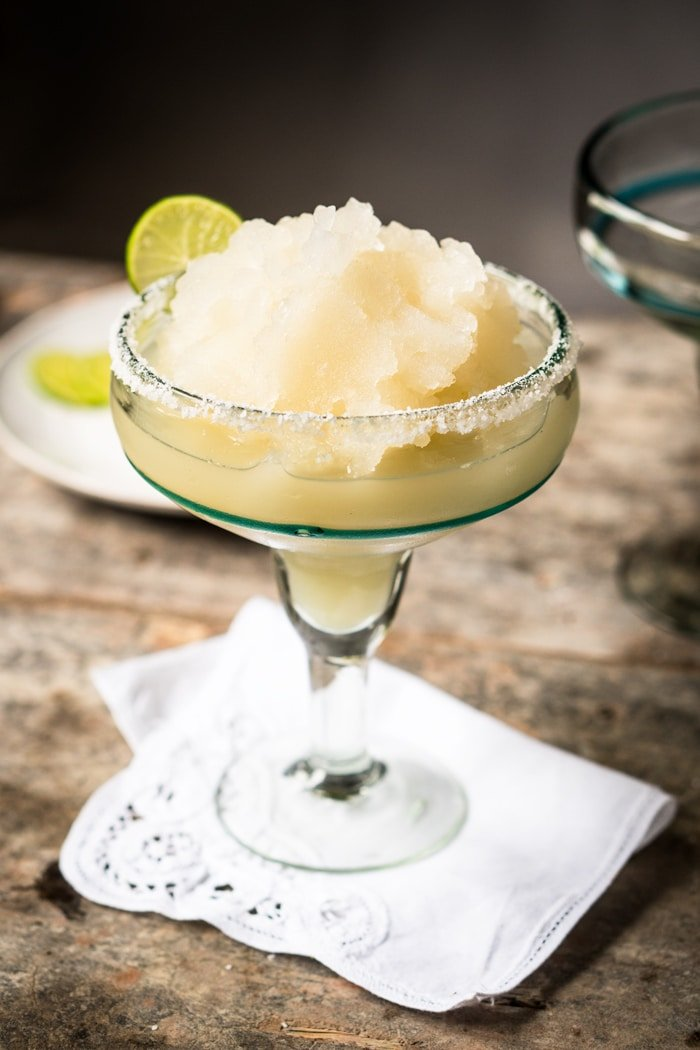 Frozen keto margarita in a tall glass with a lime wedge