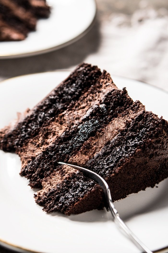 Taking a bite of a keto chocolate cake slice with a fork