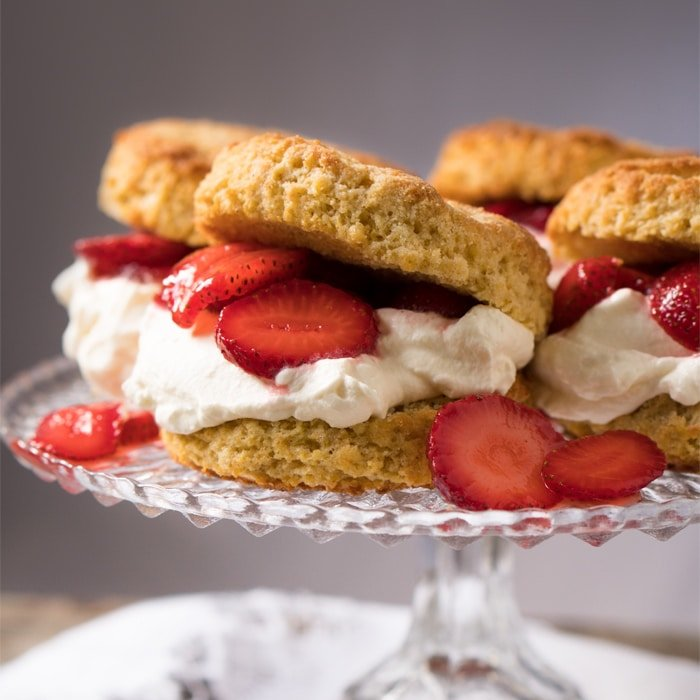 Keto strawberry shortcake with whipped cream on a cake platter