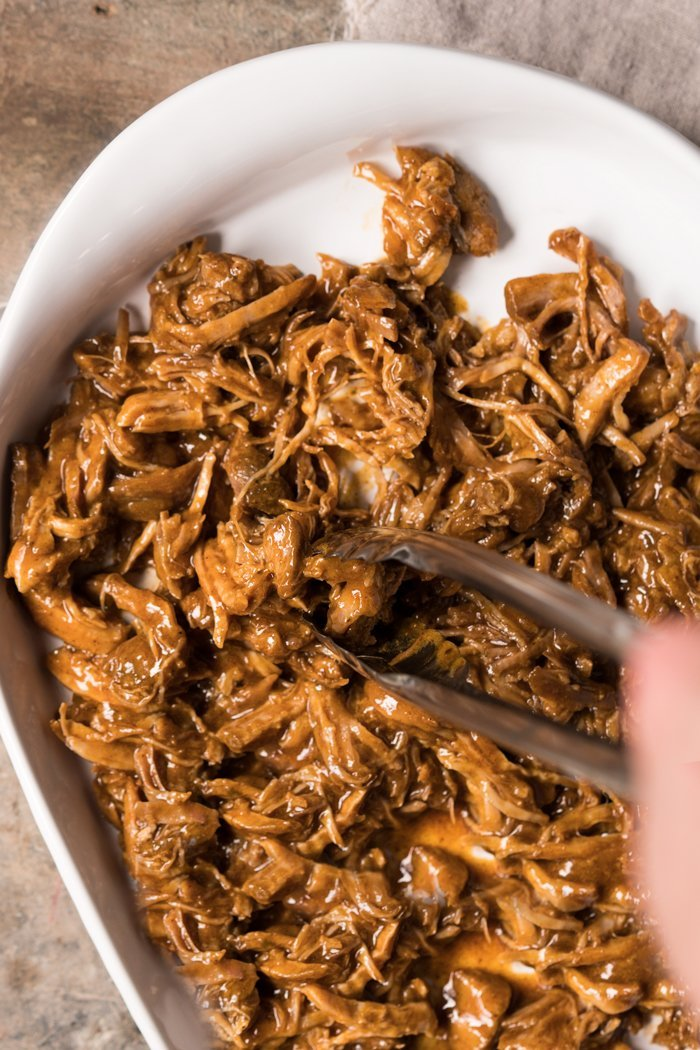 Shredding instant pot keto pulled pork in a white tray