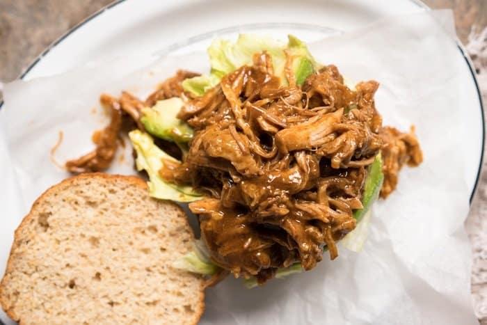 Overhead shot assembling a keto BBQ pulled pork sandwich