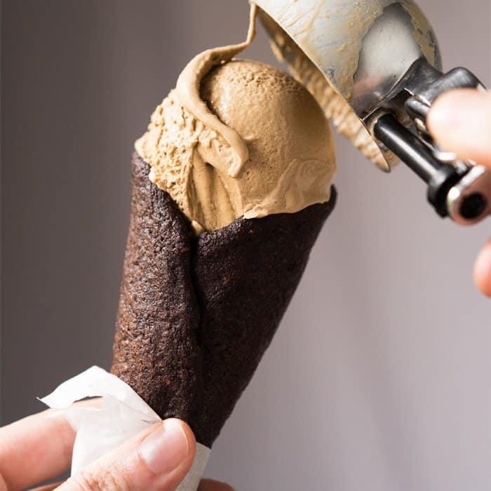 Scooping keto ice cream onto a chocolate cone