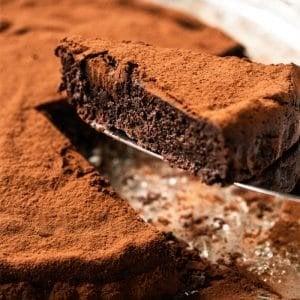 Cutting a slice of a fudgy keto flourless chocolate cake