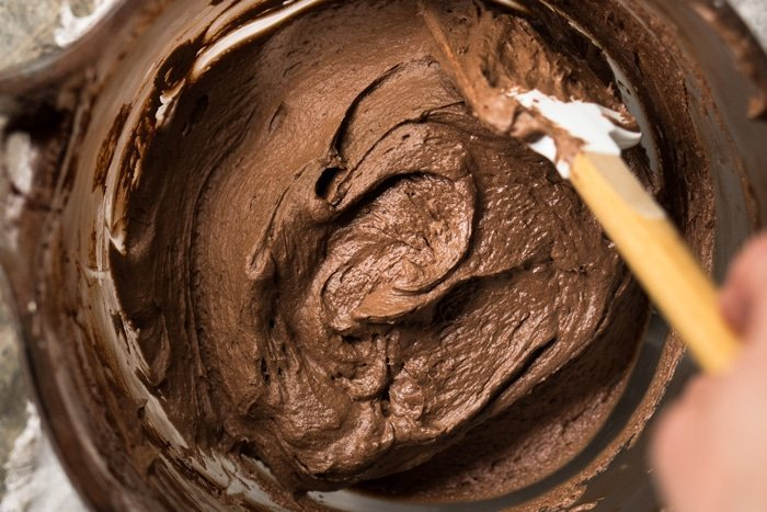 Folding the batter of a keto flourless chocolate cake