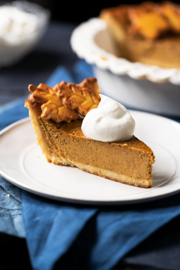 A slice of keto pumpkin pie with whipped cream
