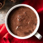Creamy keto hot chocolate in a white mug over a red napkin
