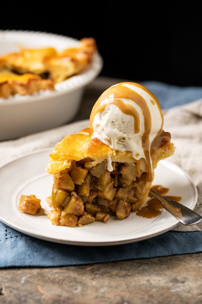 A slice of keto apple pie with vanilla ice cream and caramel