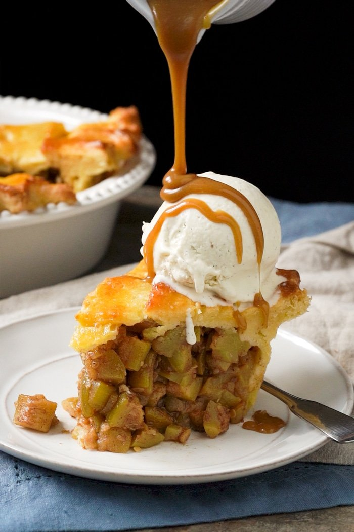 Drizzling sugar free caramel onto a slice of keto apple pie with vanilla ice cream