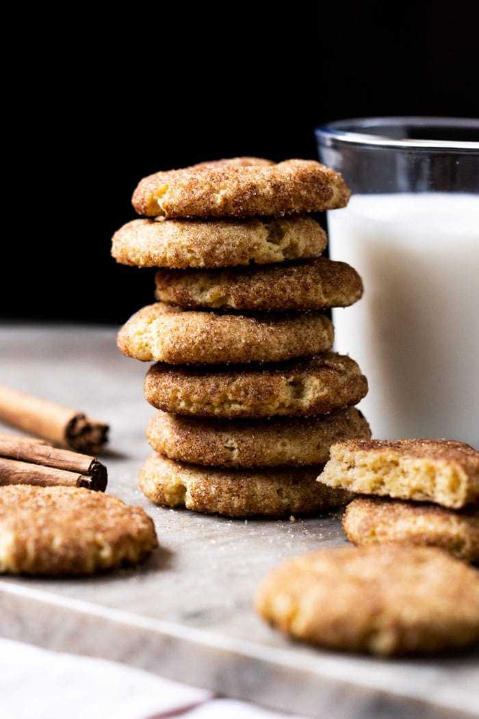 Piled up keto snickerdoodle cookies with a glass of milk