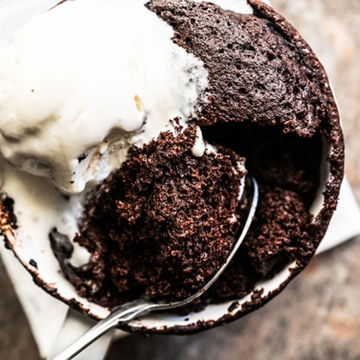 Paleo & keto mug cake with a spoon and vanilla ice cream
