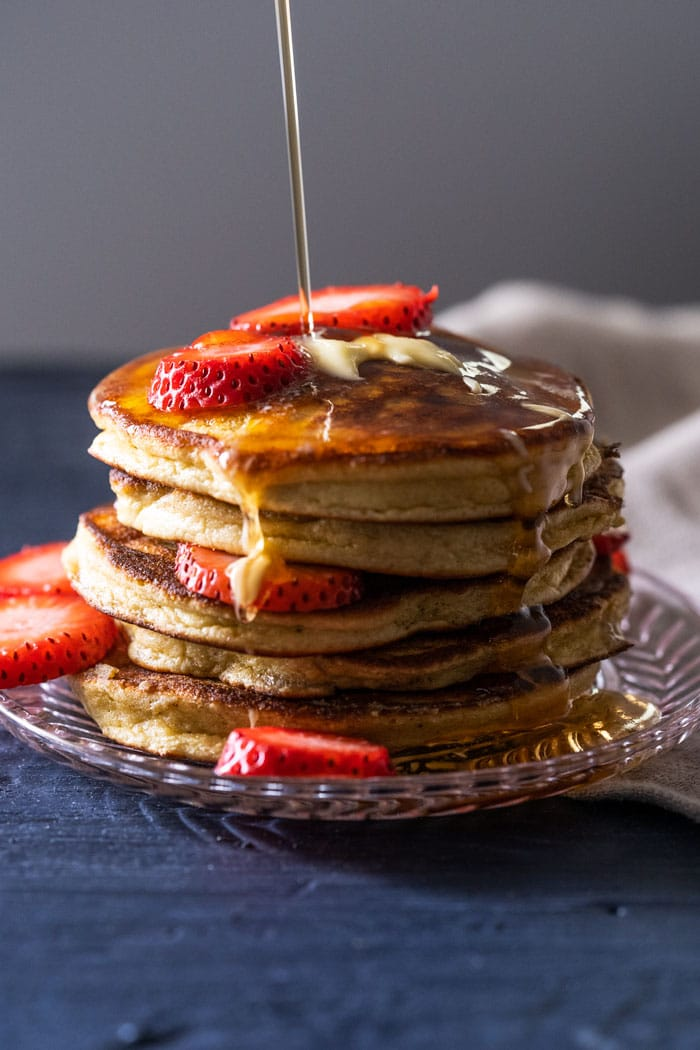 A stack of keto pancakes with sugar free syrup and strawberry slices