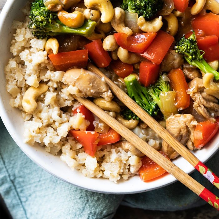 Paleo & keto cashew chicken with cauliflower rice and chopsticks