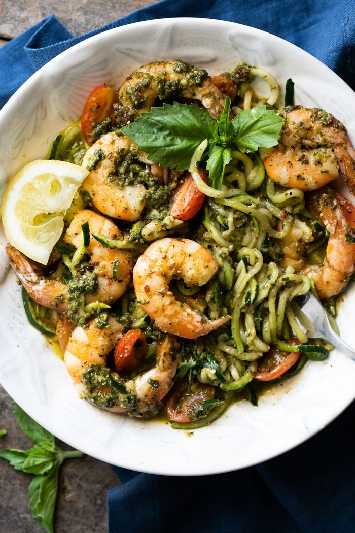 Keto zoodles with shrimp, pesto and lemon in a white bowl