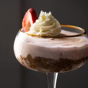 Keto strawberry cheesecake in a tall glass with whipped cream