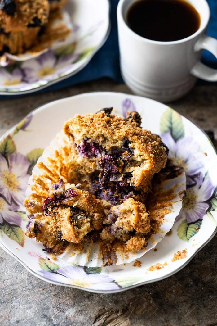 Keto muffin on a flower plate bursting with blueberries