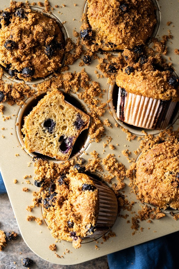 Freshly baked low carb blueberry muffins in tray with scattered streusel