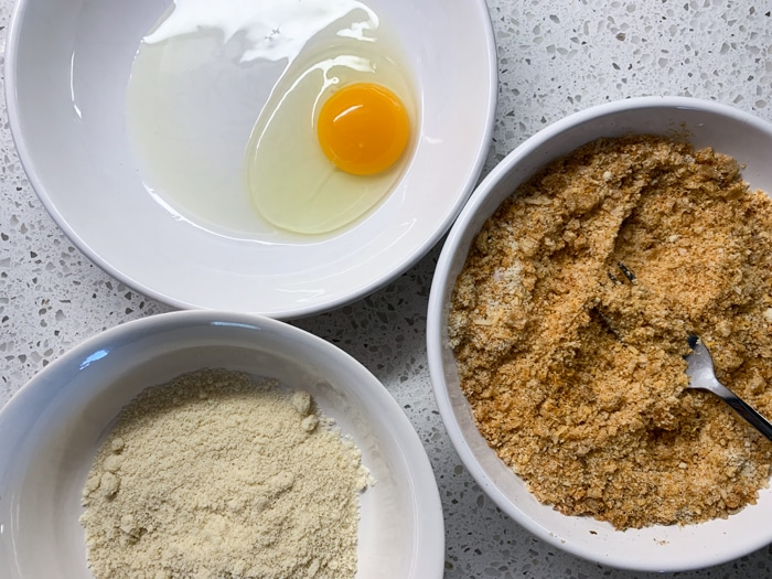 Three bowls with an egg, almond flour and crushed pork rinds