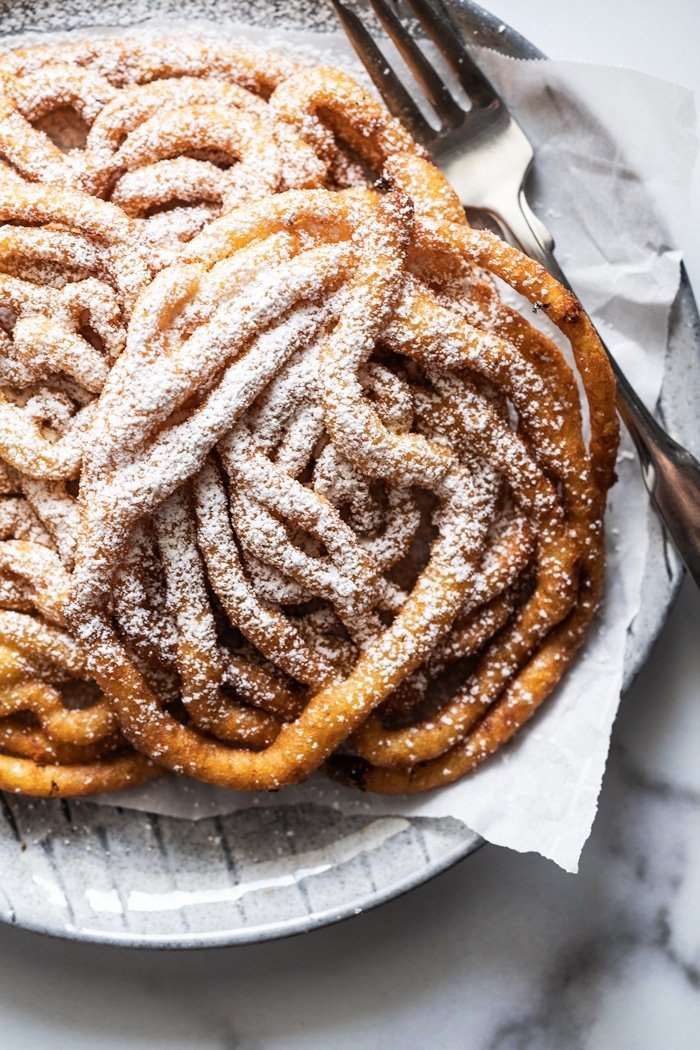 Keto funnel cakes with powdered 'sugar', on a plate with a fork