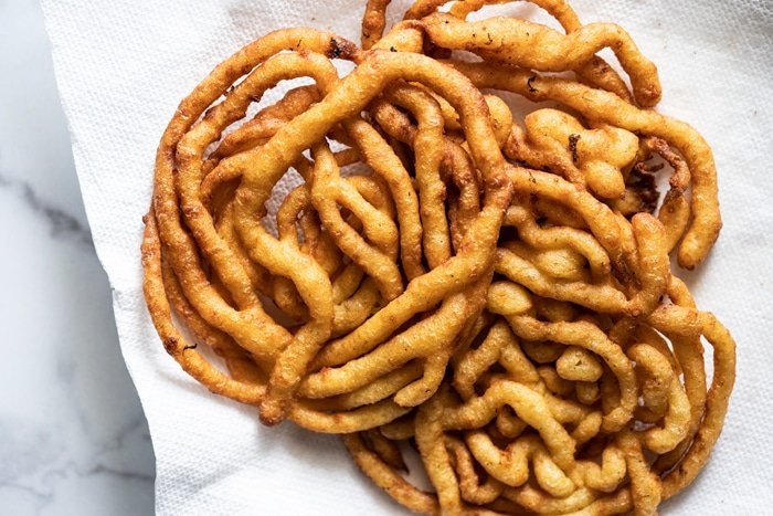 Freshly fried keto funnel cakes on a paper towel