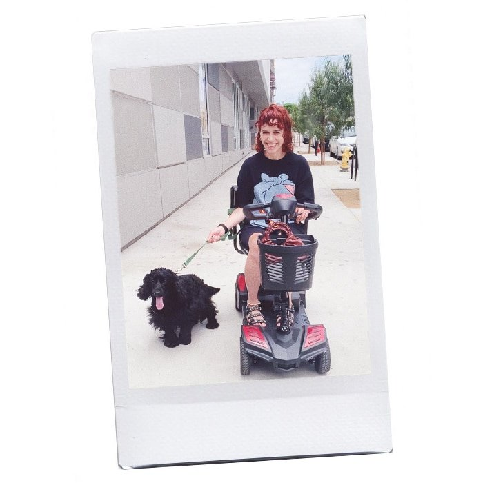 Paola with her dog Dedal in an electric scooter
