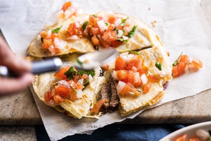 Topping the keto quesadillas with pico de Gallo salsa