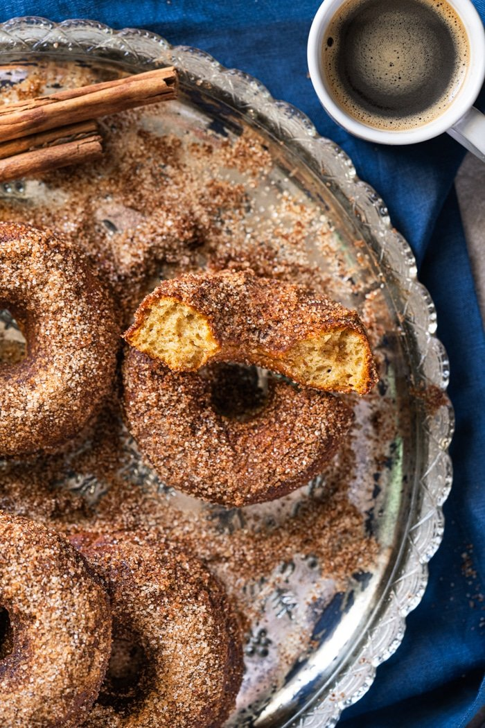 Keto apple cider donuts on a silver platter with a mug of coffee