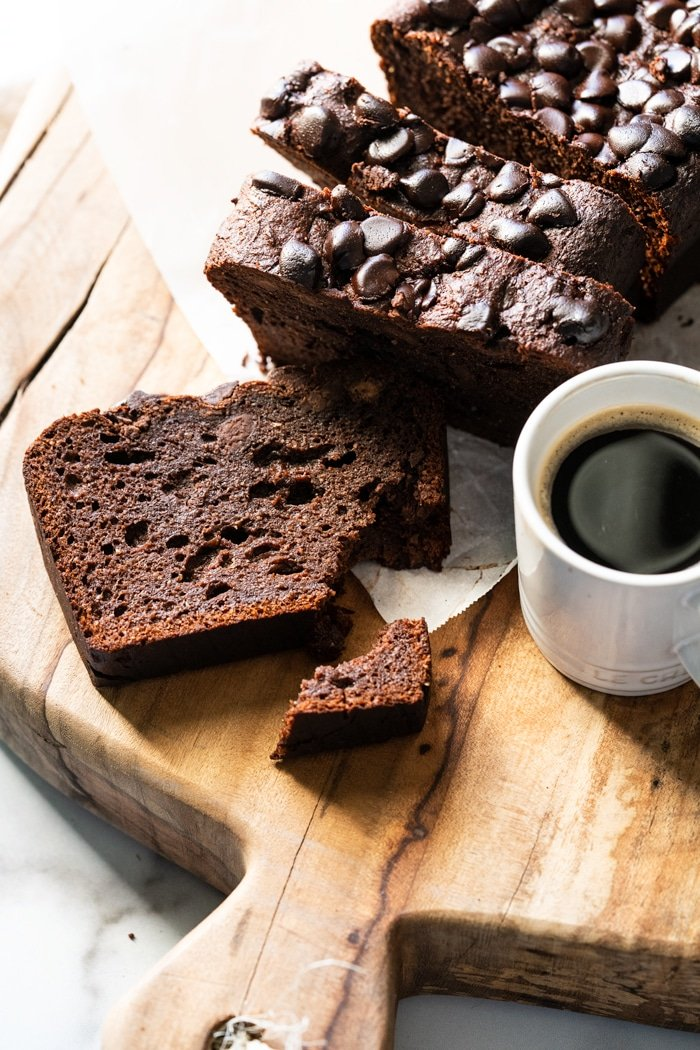 Closeup slice of Keto chocolate zucchini bread on a wooden board with coffee on the side