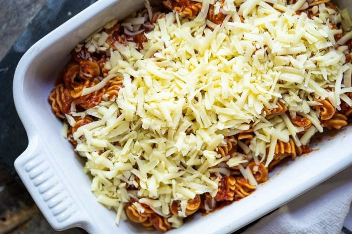 Adding grated mozzarella to the Keto pasta bake