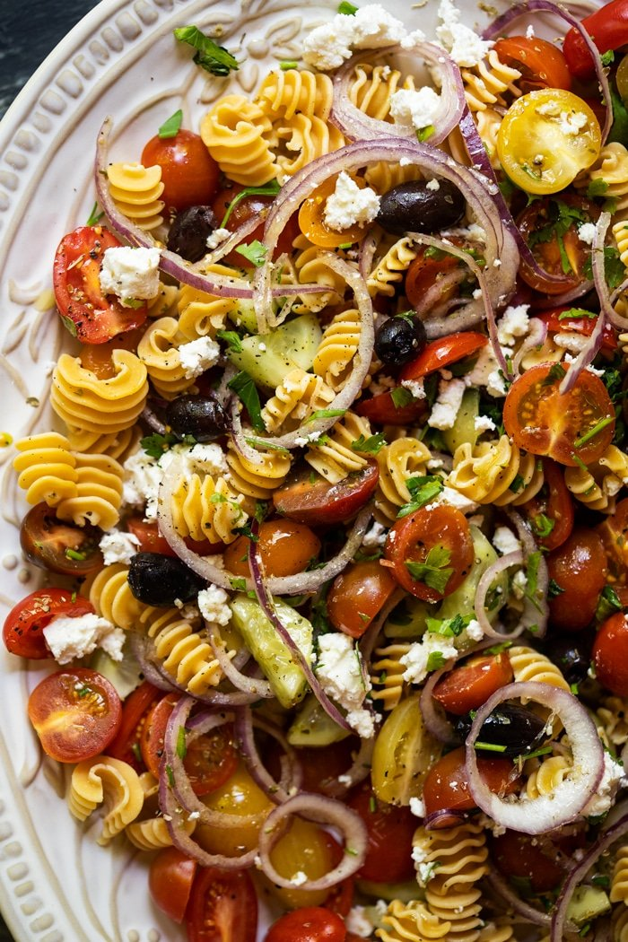 Keto pasta salad with cherry tomatoes, cucumber and olives on a white serving platter