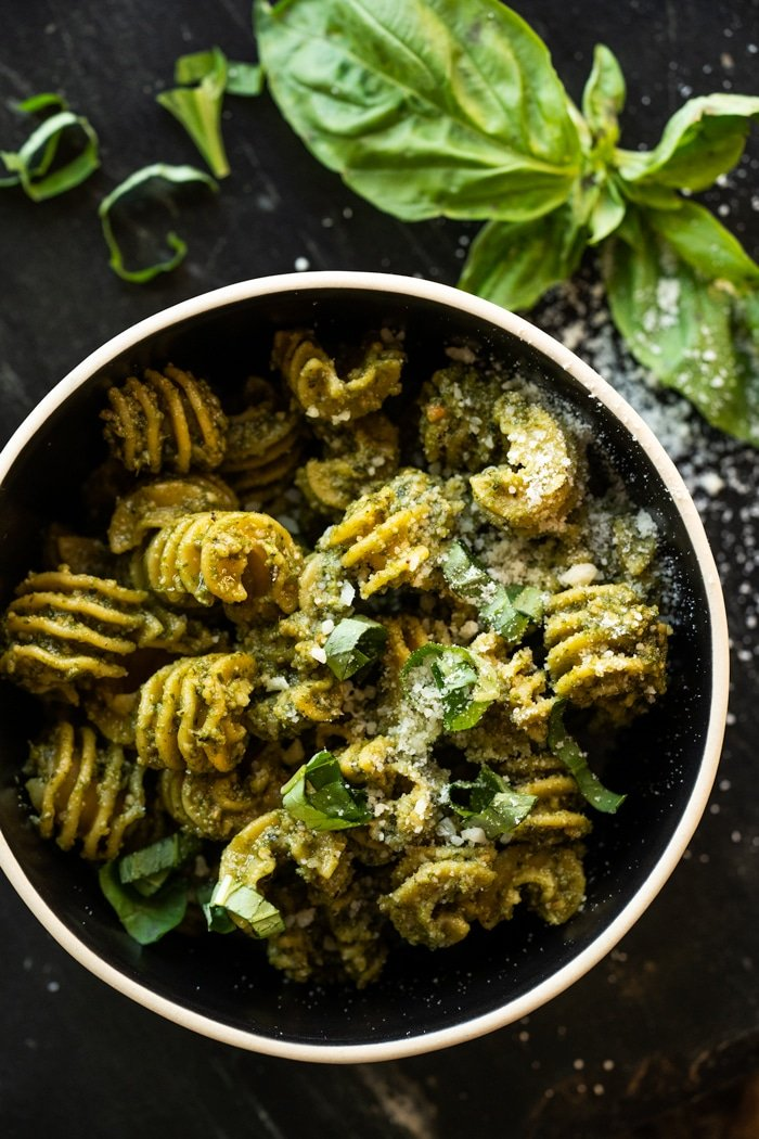 Keto pesto pasta with fresh basil and parmesan cheese in a black bowl