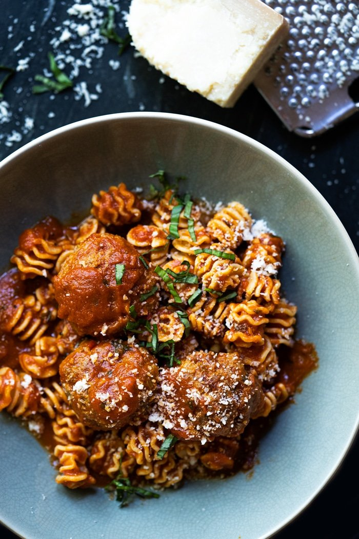 Bowl of Keto meatballs with radiatori pasta, Parmesan cheese and basil