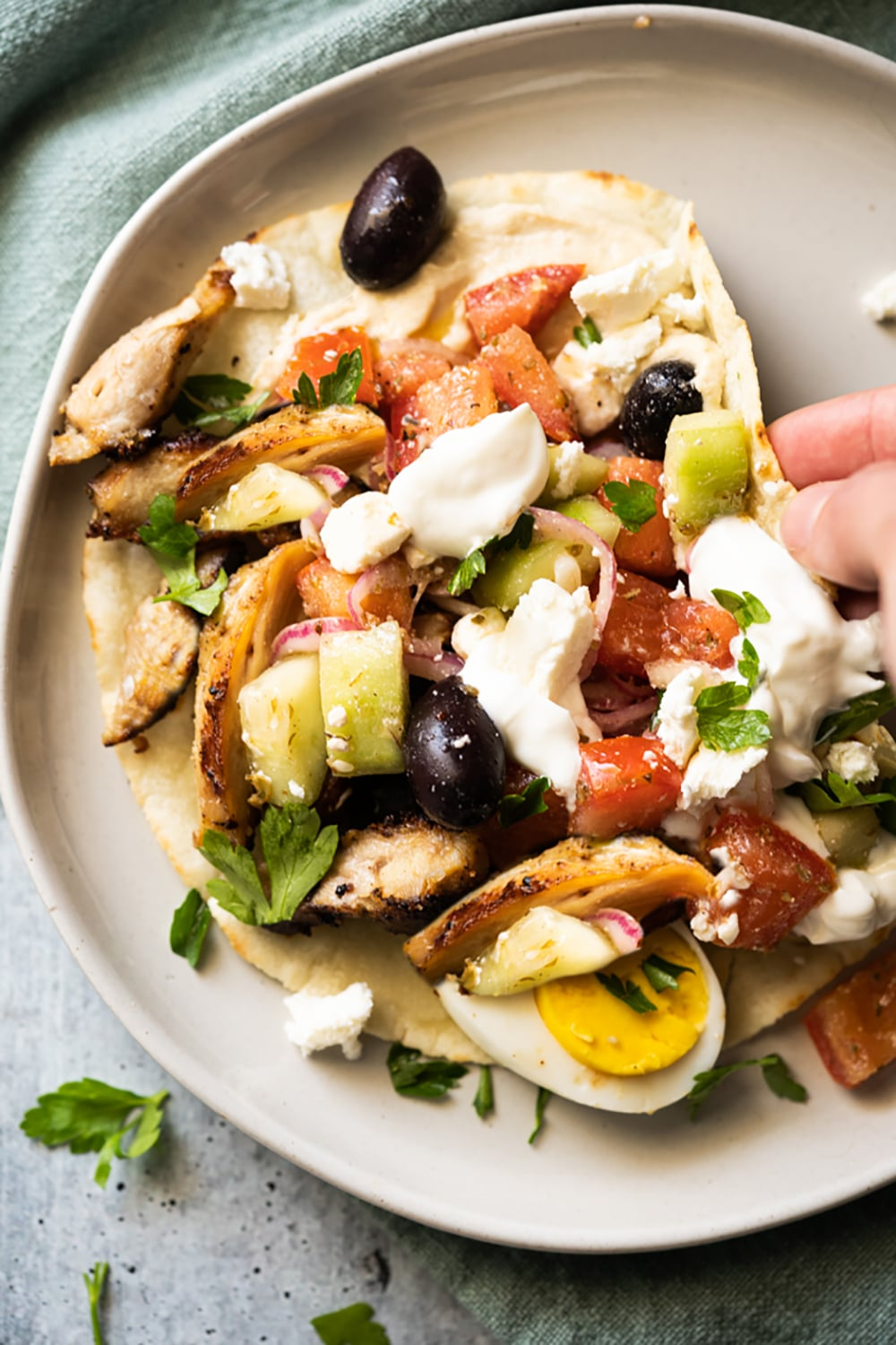 Folding a keto chicken wrap with tomatoes, eggs, cucumber, olives and feta cheese