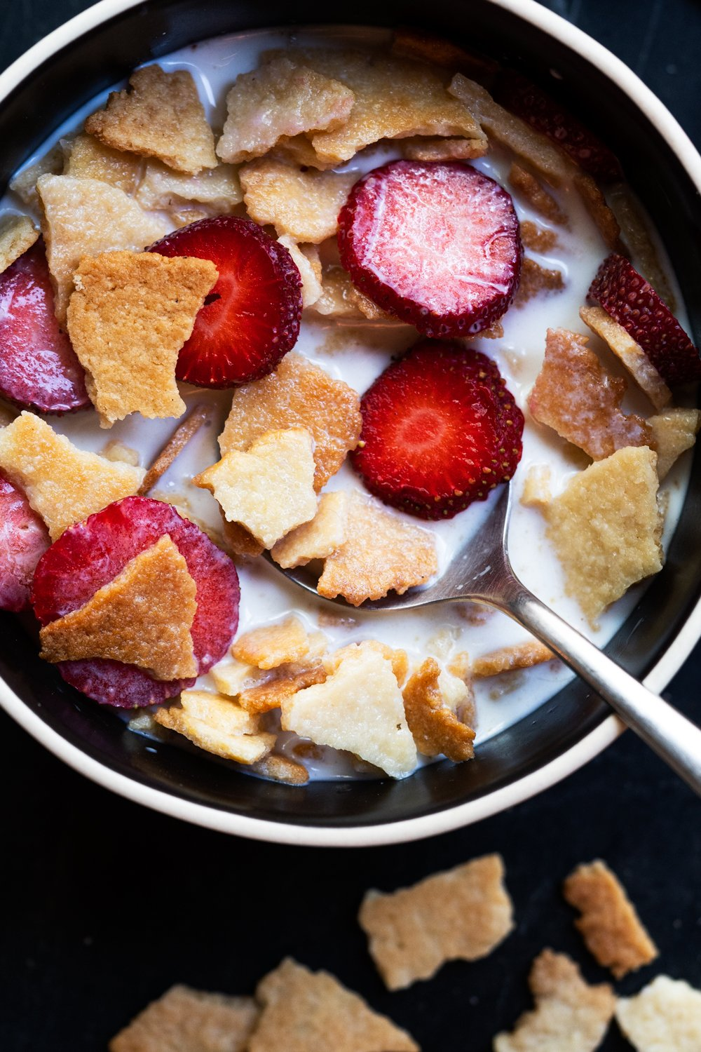 Keto Frosted Flakes cereal with sliced strawberries and almond milk in a black bowl