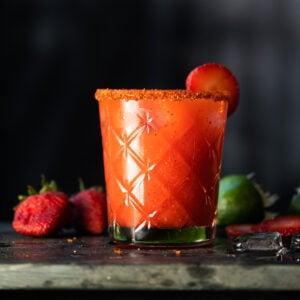 A paleo and keto strawberry margarita with a spicy Tajin rim