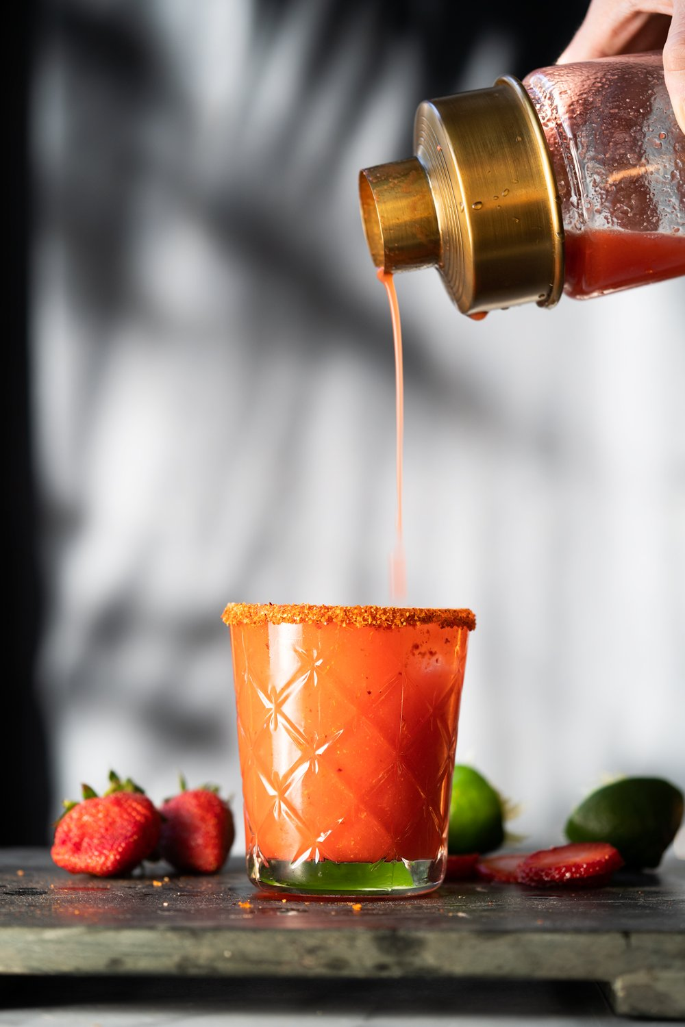 Pouring a paleo and keto strawberry margarita from a glass shaker