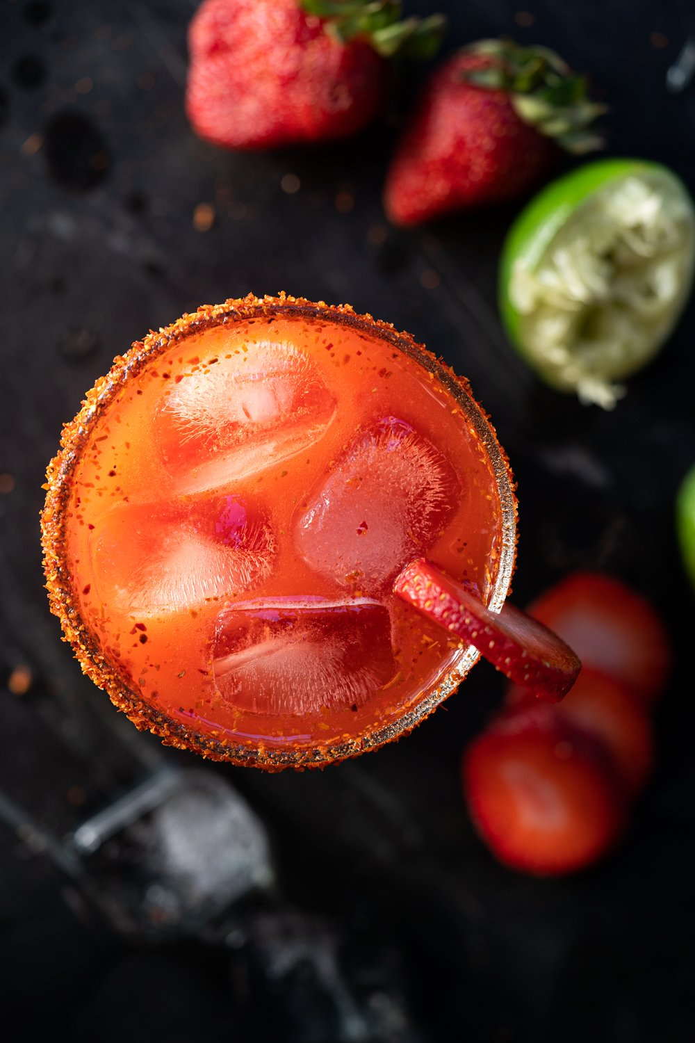 Overhead shot of a keto strawberry margarita with limes and strawberries scattered around it