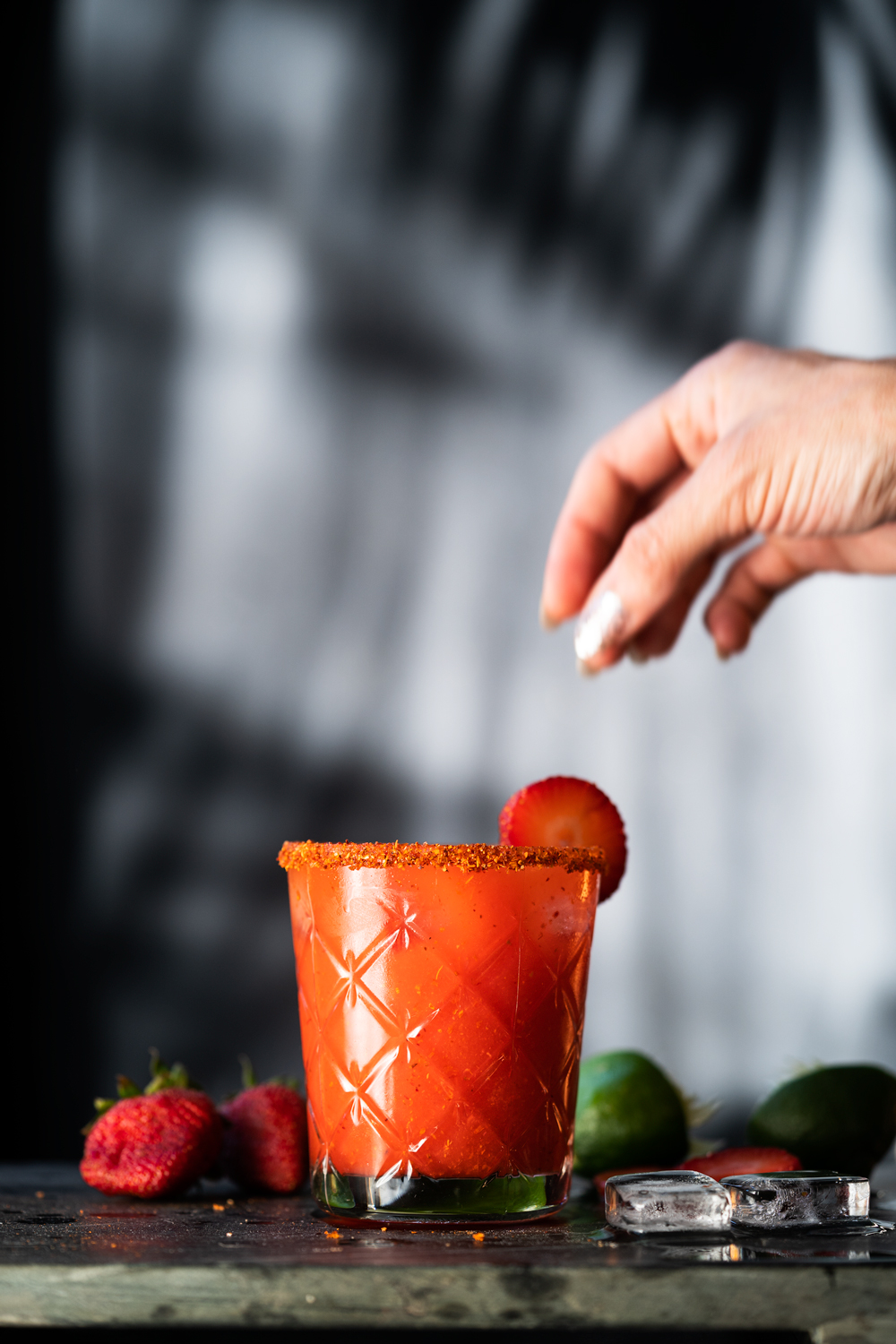 Placing a strawberry slice on the rim of a paleo strawberry margarita