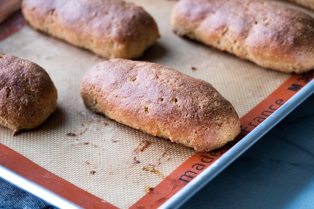 Freshly baked Keto hot dog buns on a baking tray