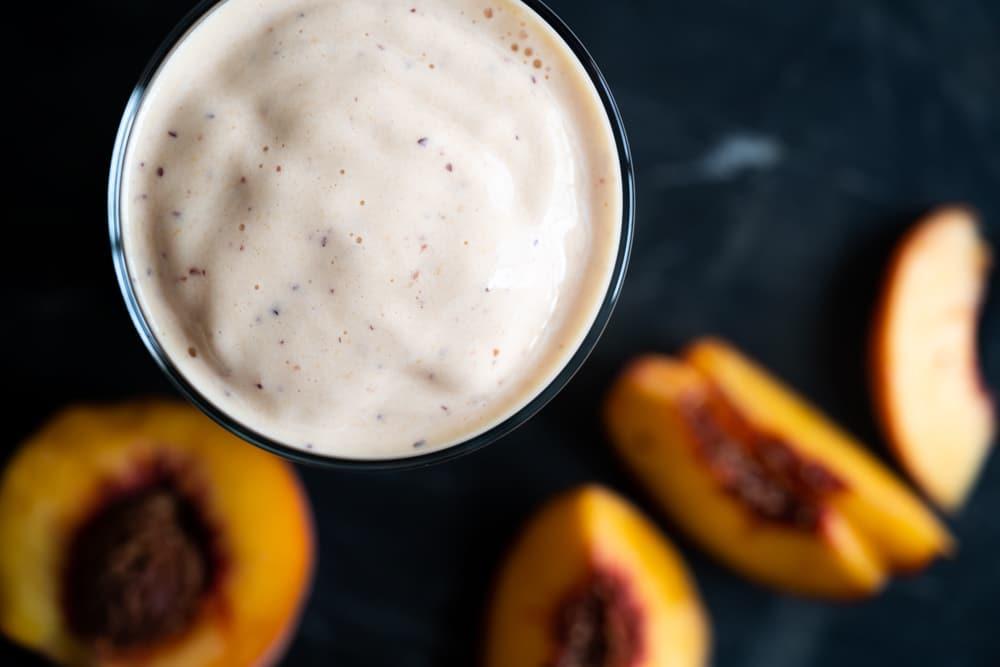 Overhead shot of a keto peach milkshake showing its luscious texture