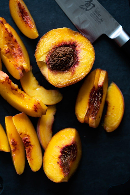 Slicing peaches on a black cutting board