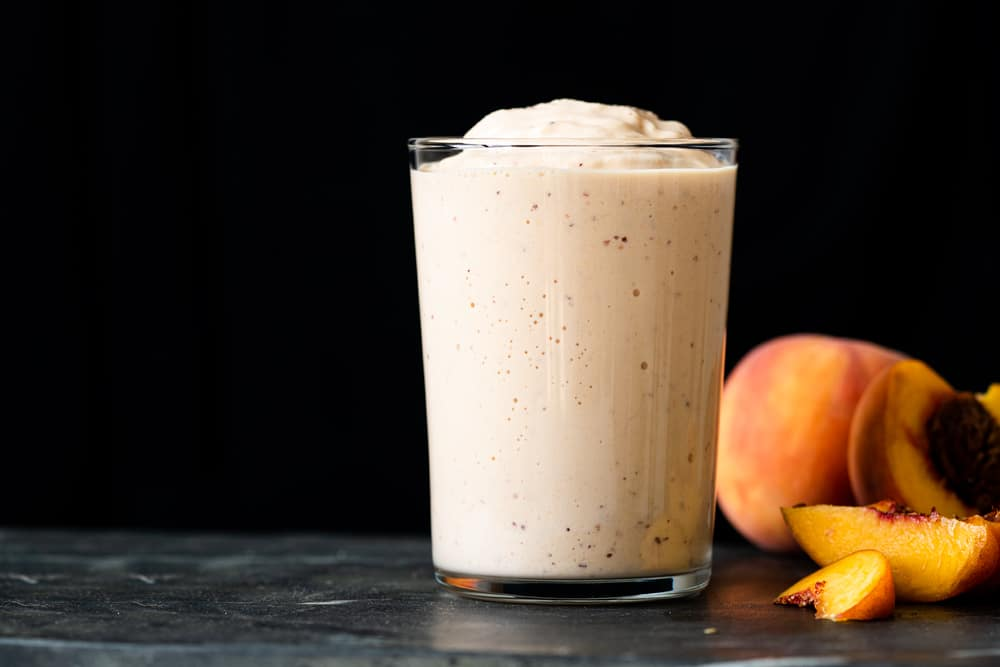 Side shot of a keto peach milkshake in a glass showing its thick texture
