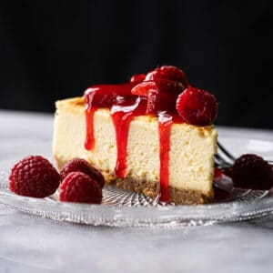 Keto cheesecake slice with a graham cracker crust, berries and strawberry jelly
